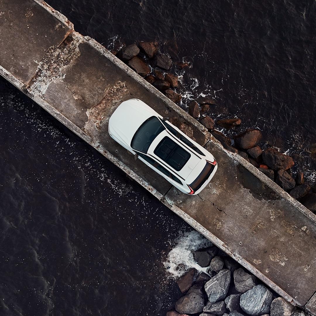 Een witte Volvo XC60 Recharge staat geparkeerd op een schip dat omgeven is door de zee