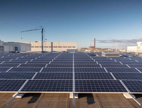Mange solcellepaneler foran en fabrikkbygning.