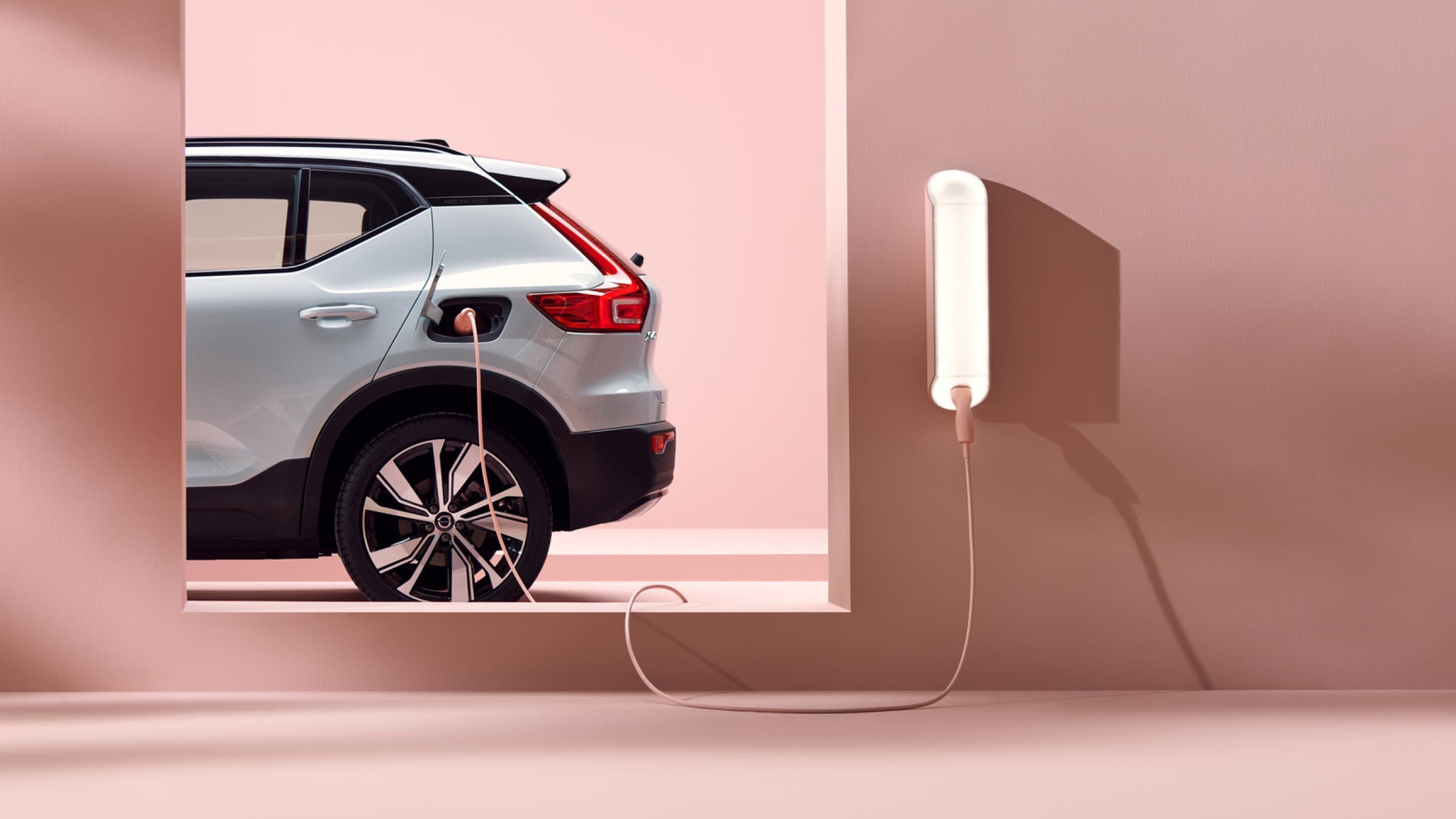 En sølvfarget Volvo XC40 Recharge elektrisk SUV, til opplading i rosa omgivelser.