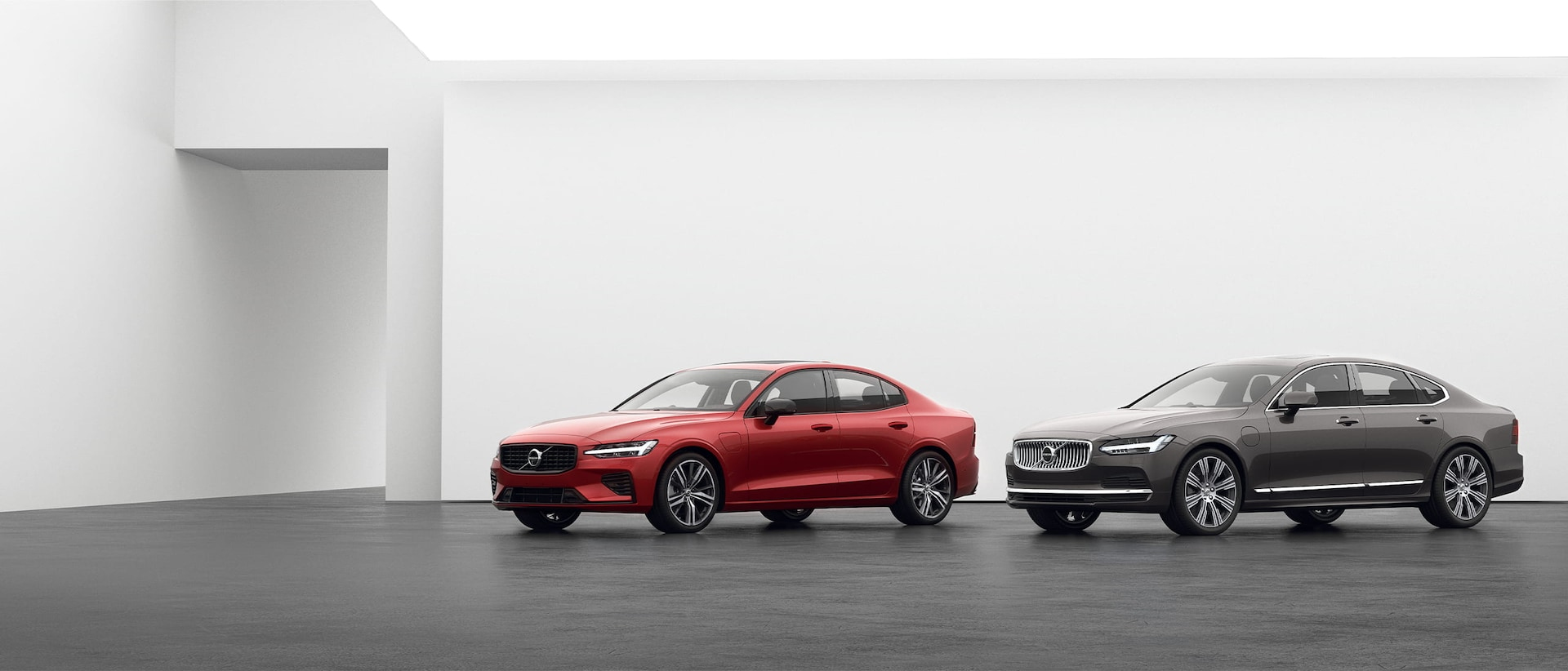 A Volvo S90 and a Volvo S60 Recharge plugin hybrid parked on grey floor
