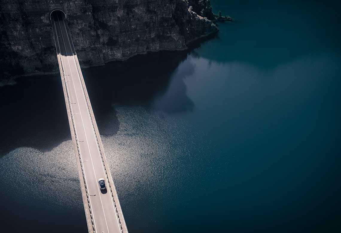 En Volvo passerer en bro over et vann.