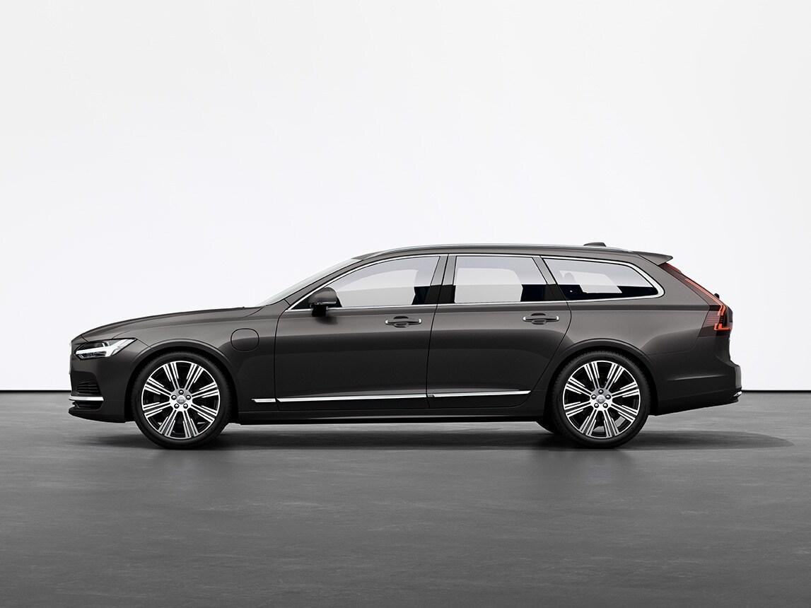 A pine grey Volvo Estate V90 Recharge plugin hybrid standing still on grey floor in a studio