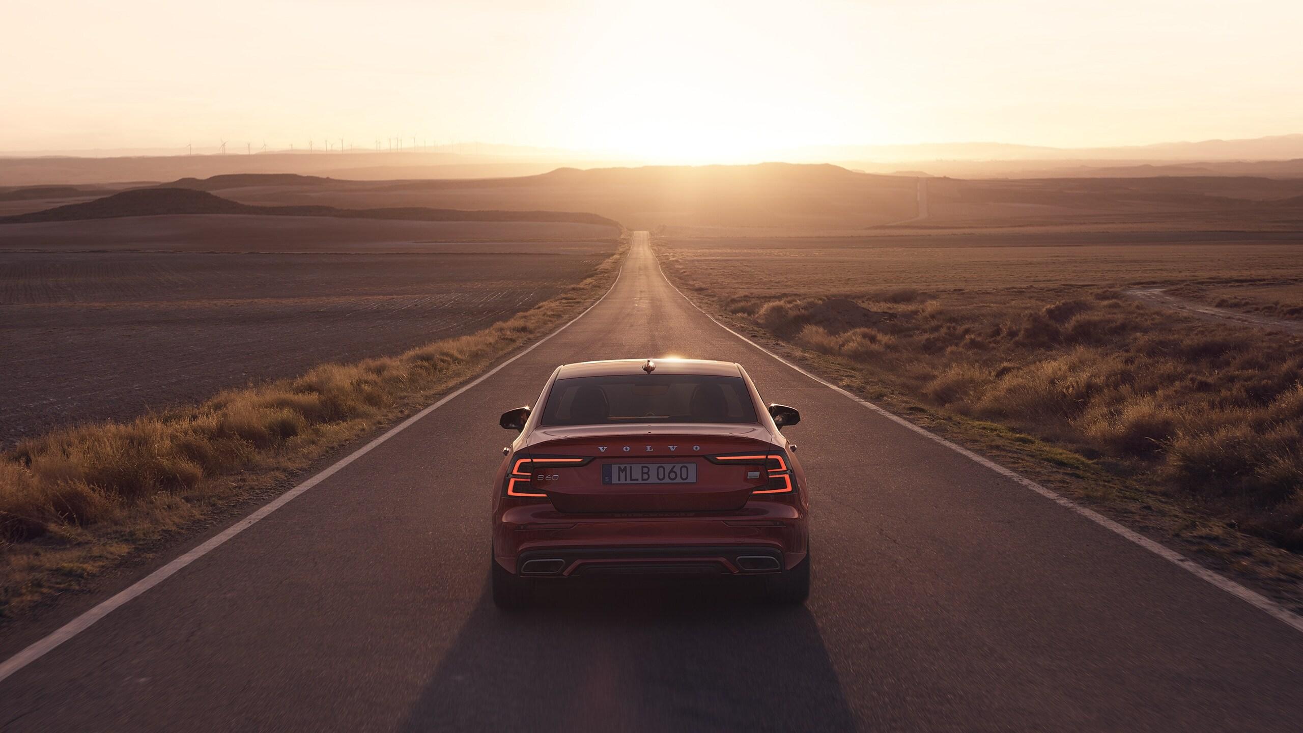 En rød Volvo S60 Recharge kjører på en vei i solnedgang.
