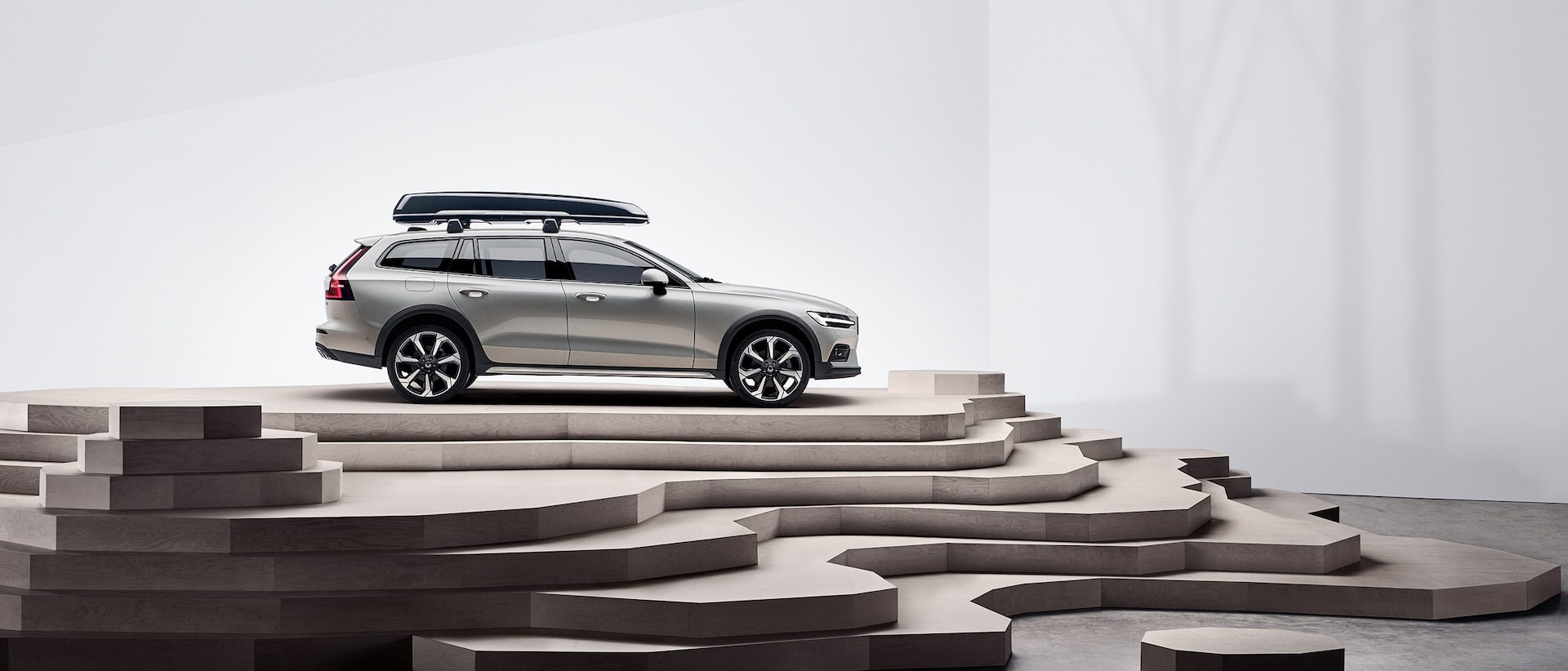 En beige Volvo V60 Cross Country med takboks, parkert på toppen av en trapp.