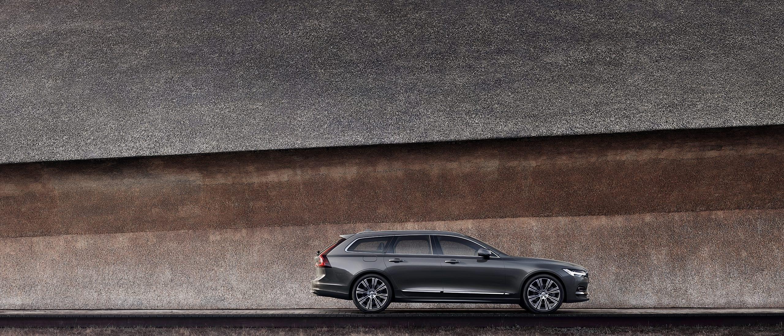 En mørkegrå Volvo V90, parkert ved en vegg.