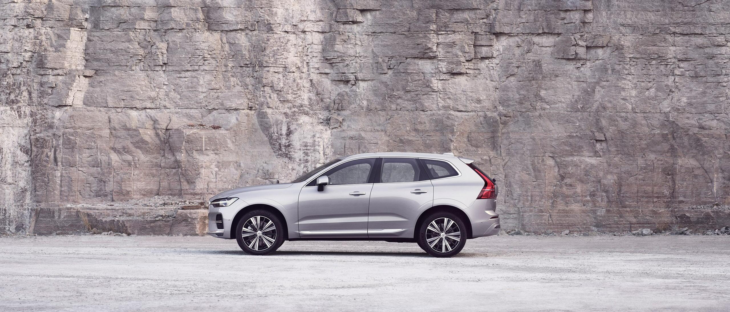En sølvfarget Volvo XC60, parkert foran en fjellvegg.