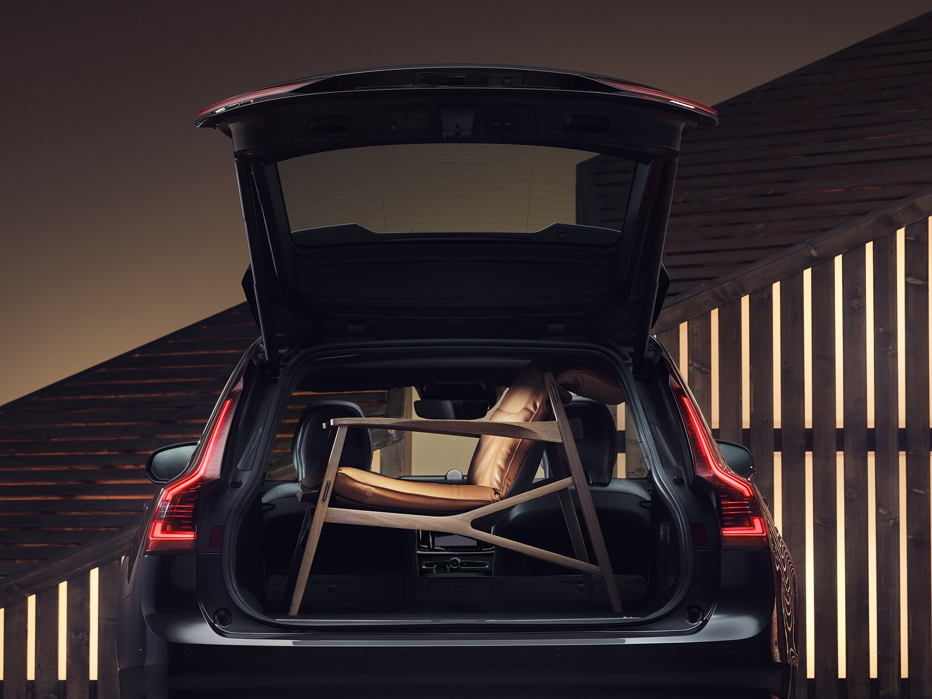 The boot space of a Volvo V90, filled up by a brown elegant armchair
