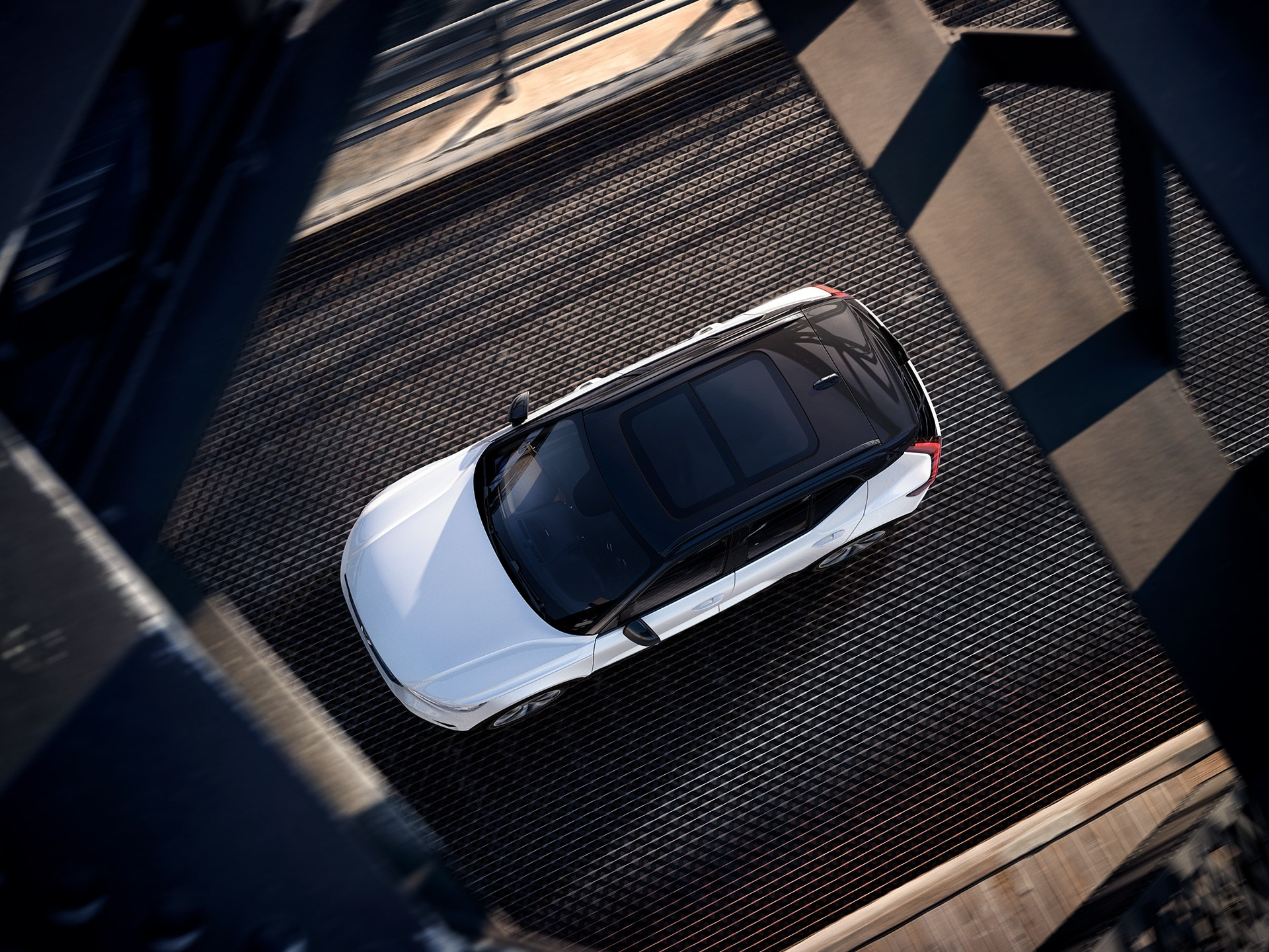 A white XC40 Recharge plug in hybrid from above, driving on a bridge