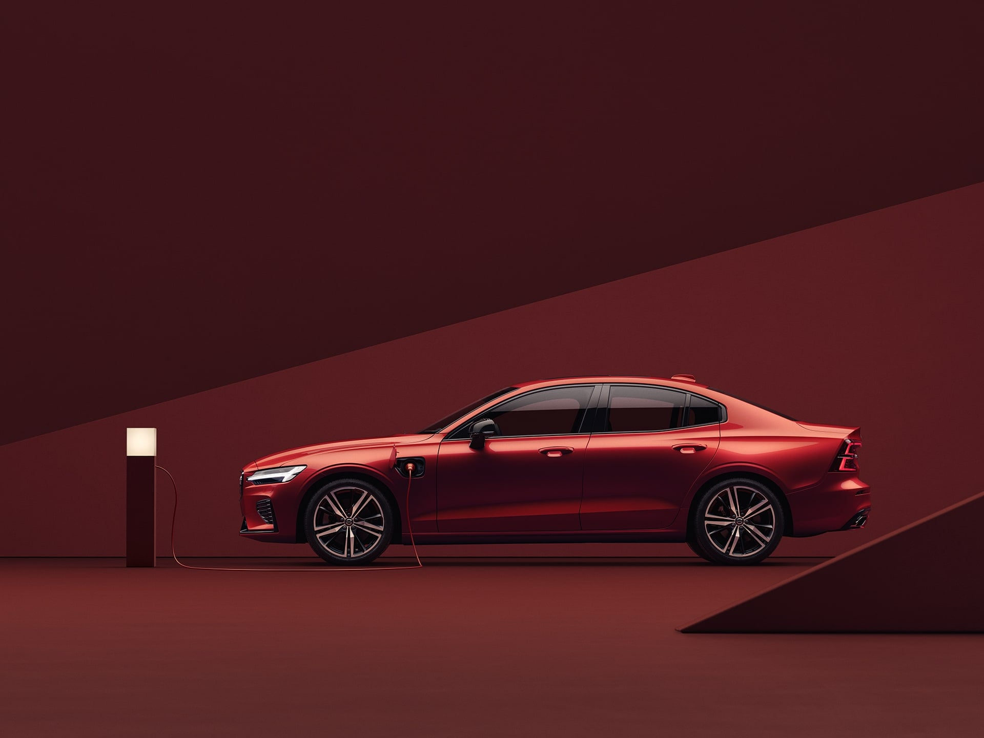 The front exterior of a red Volvo S60 Recharge Plug-in hybrid sedan in a red surrounding.