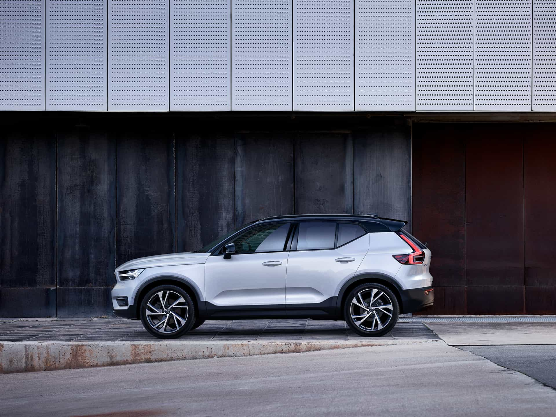 A white Volvo XC40 SUV is parked outside a building.