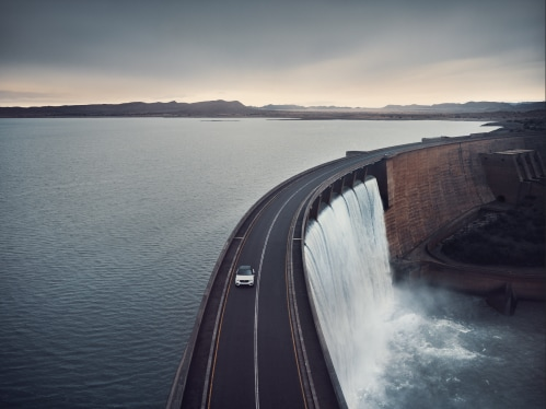 Volvo SUV drives on a bridge that crosses a water reservoir.