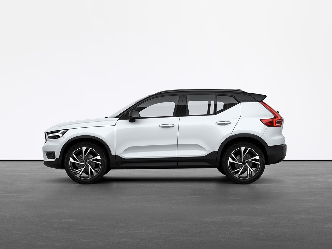 A crystal white Volvo XC40 compact SUV standing still on grey floor in a studio