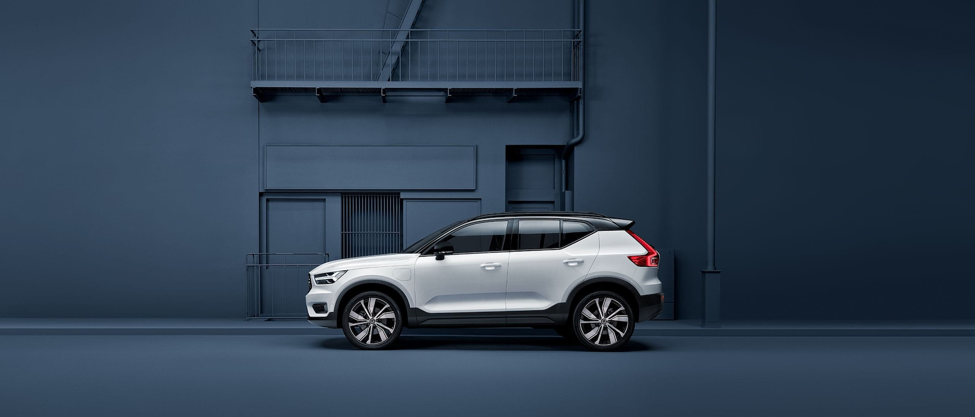 A white Volvo XC40 Recharge plug-in hybrid stands parked alongside a blue facade.