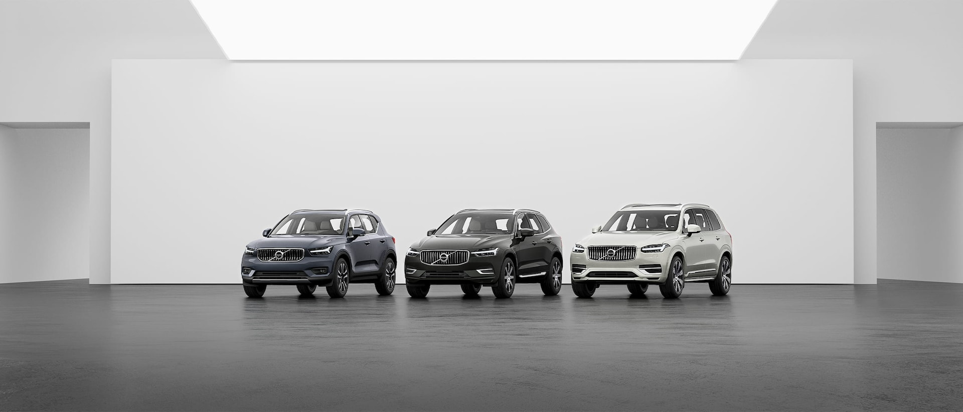 A lineup of Volvo SUVs, XC40, XC60 and XC90 on a grey floor