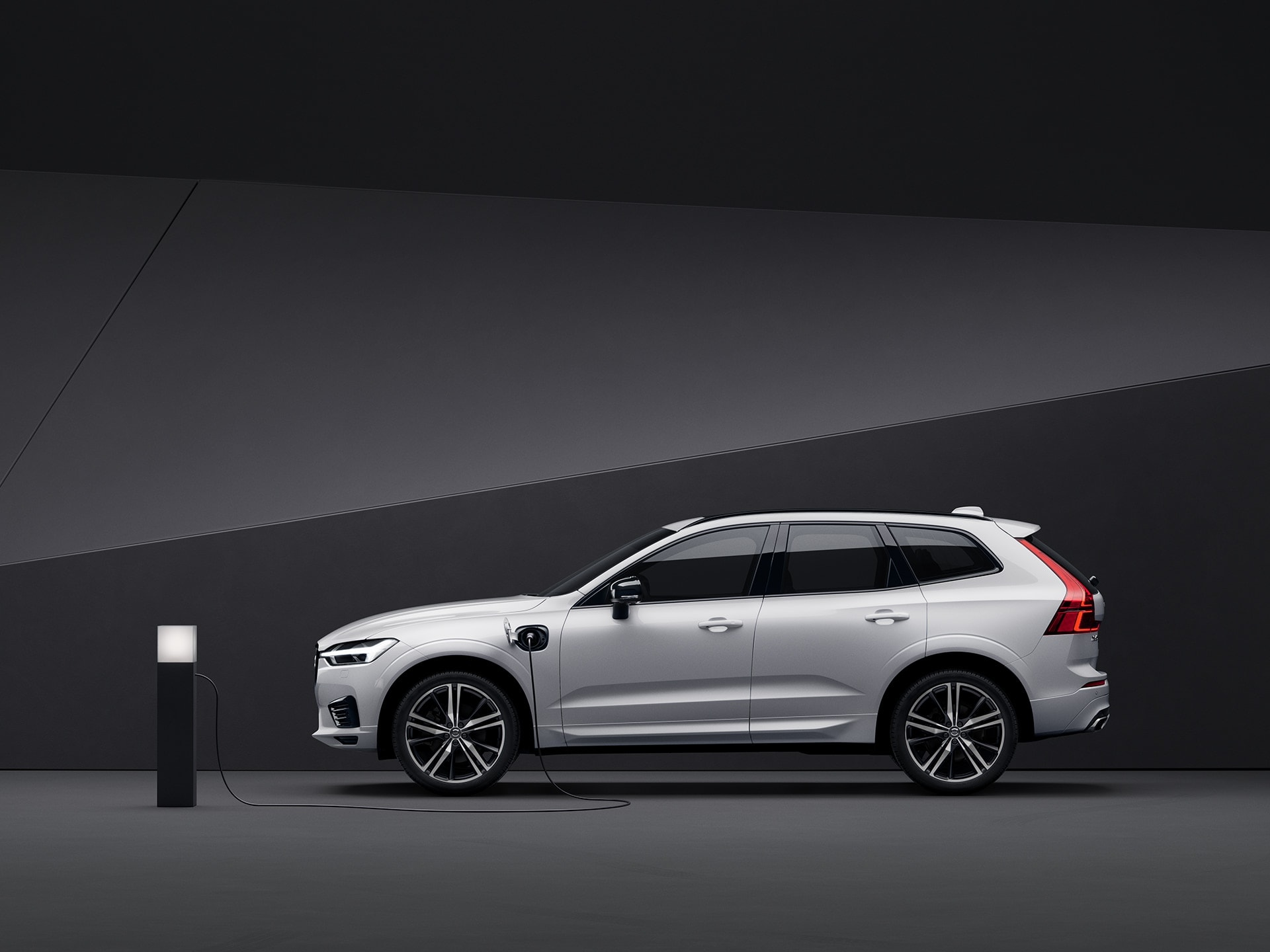 A white Volvo XC60 Recharge charges in a black surroundin