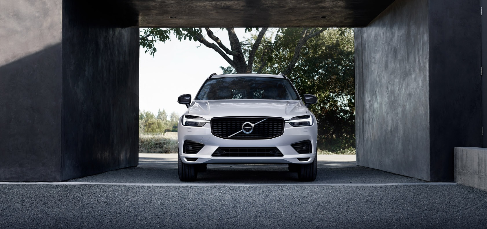 A white Volvo XC60 is parked next to a concrete building