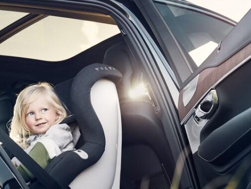 Fotelik dla dziecka zwrócony tyłem do kierunku jazdy i mała dziewczynka siedząca na tylnym siedzeniu samochodu Volvo.