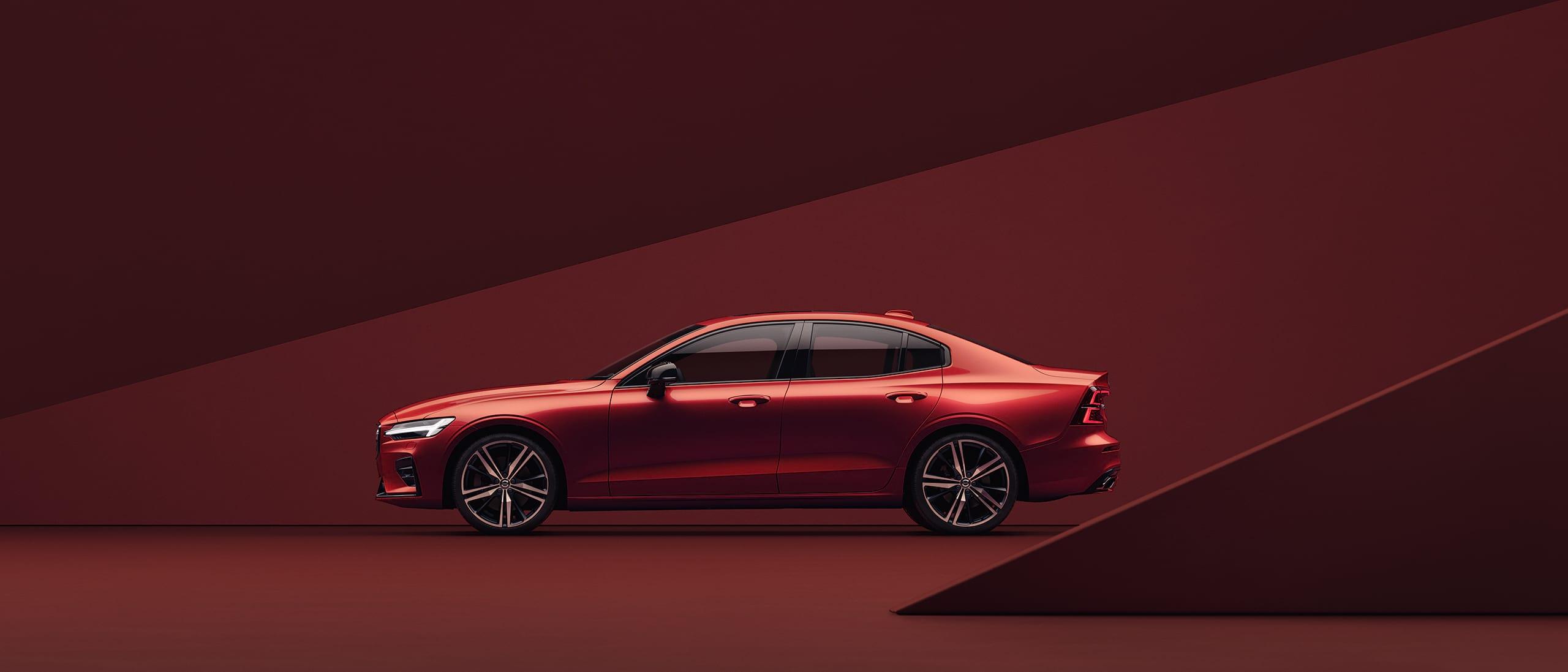 Czerwone Volvo S60, zaparkowane wczerwonym otoczeniu.