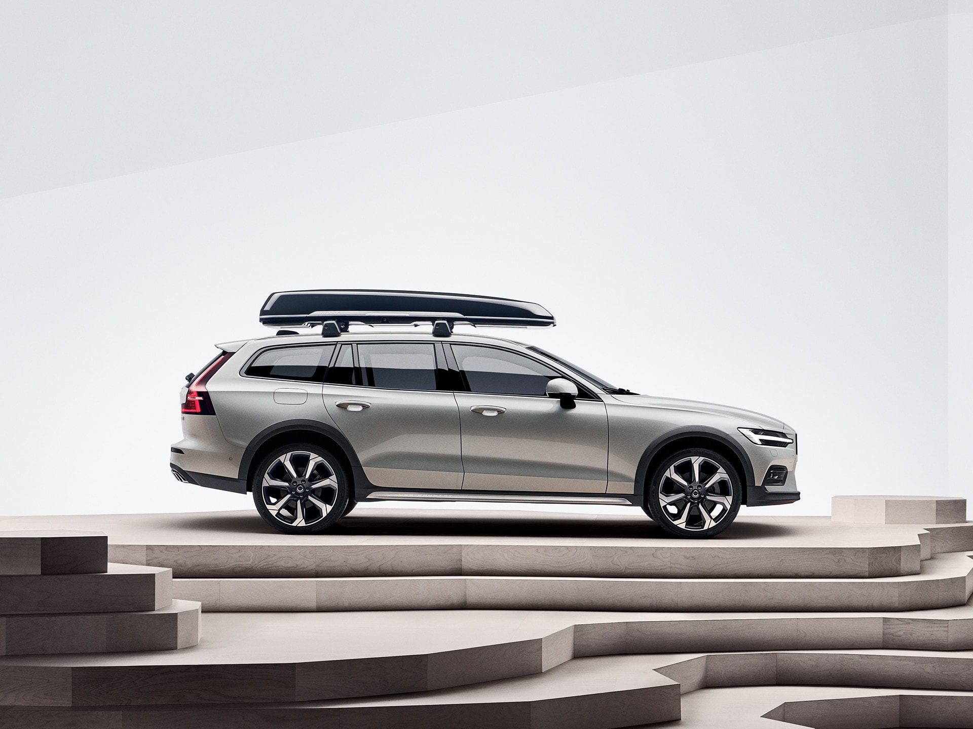 A beige Volvo V60 Cross Country with a roof box is parked on top of a staircase