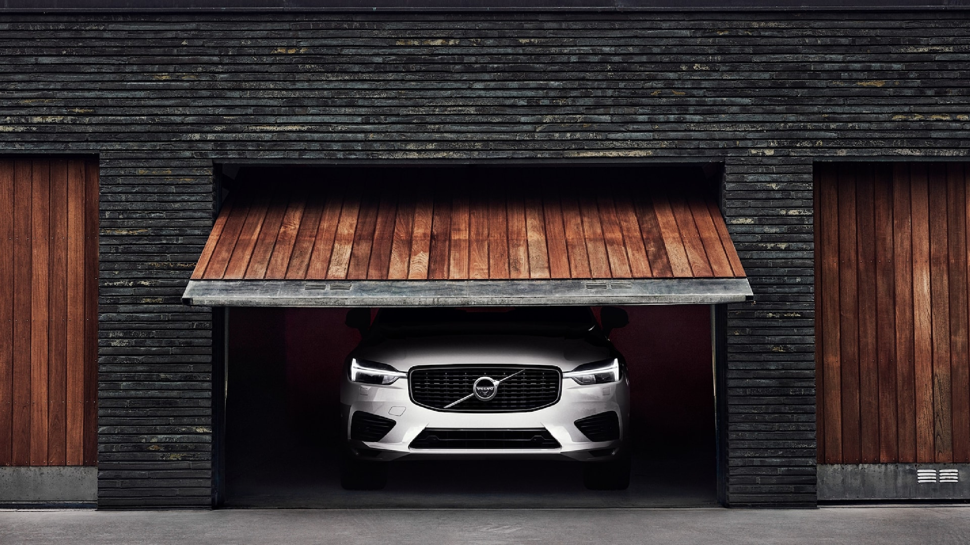 XC60 standing inside a garage, while the wooded front gate is opening.