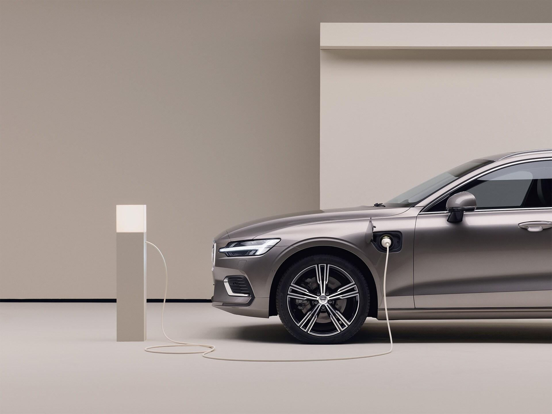Uma carrinha Volvo cinzenta estacionada está ligada a um ponto de carregamento