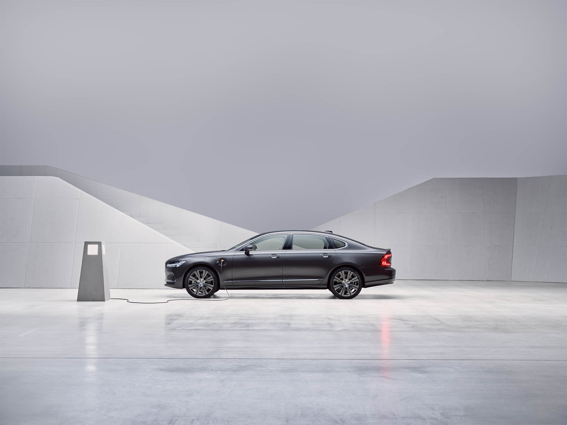 Um sedan Volvo S90 híbrido plug-in Pebble Grey parado e a carregar