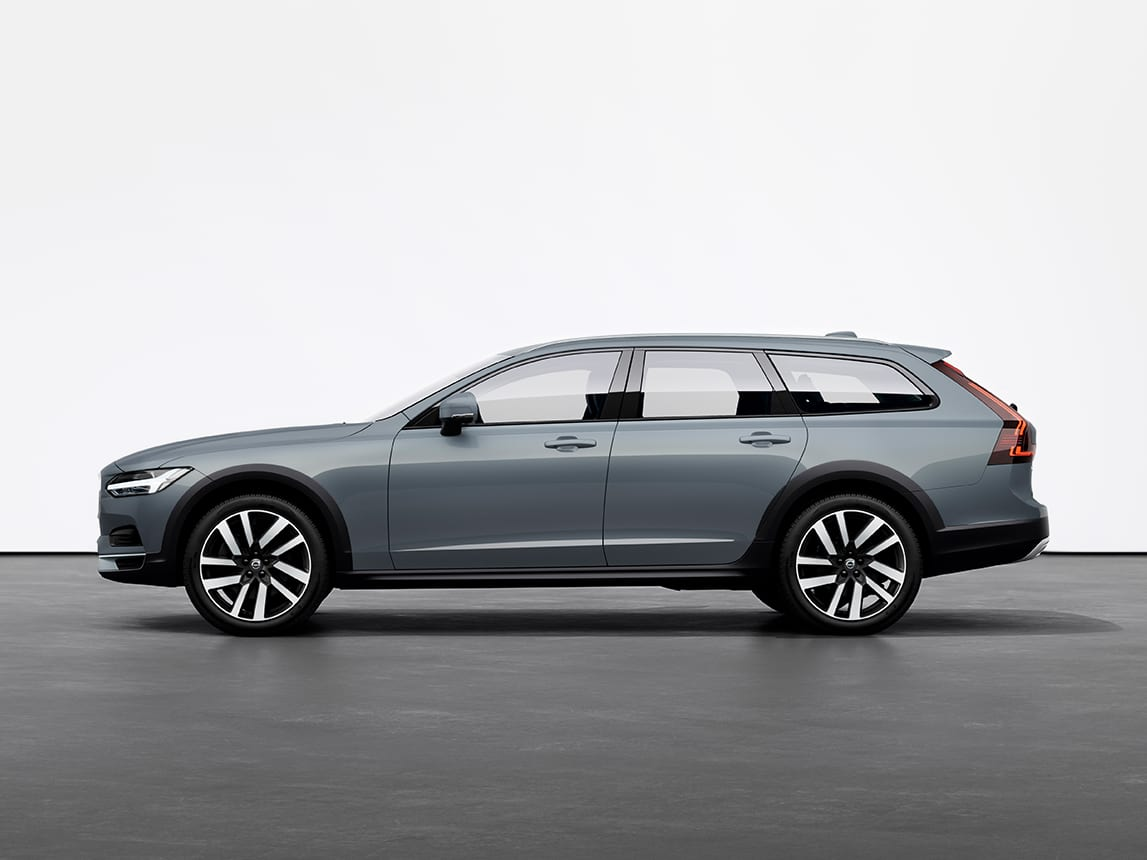 A mussel blue metallic Volvo V90 Cross Country Estate standing still on grey floor in a studio