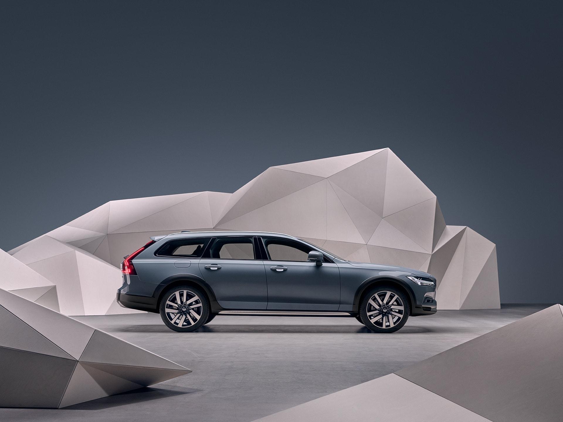 Uma Volvo V90 Cross Country na cor Azul Mussel metalizado parada em frente a uma parede artística