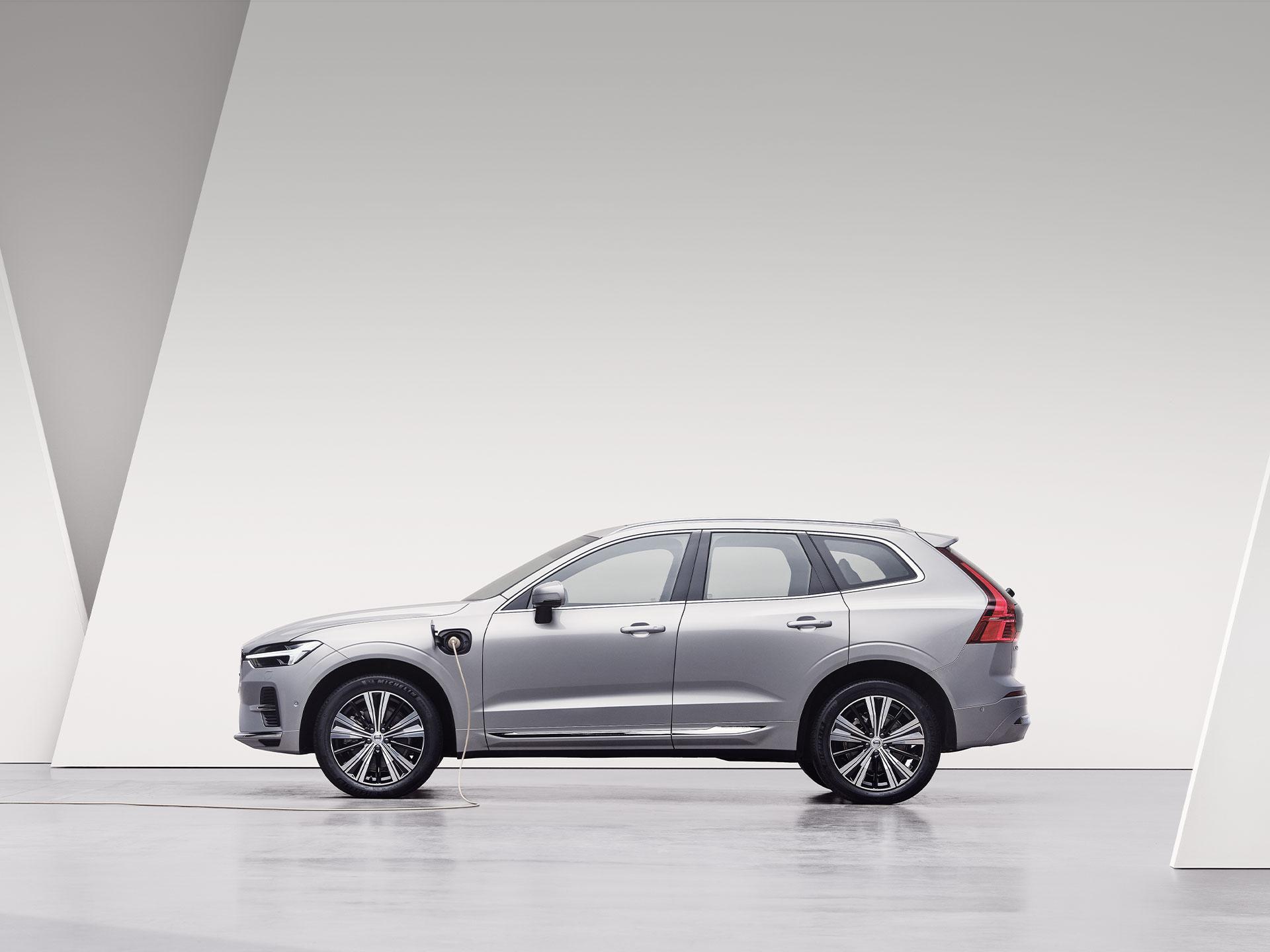 Un Volvo XC60 Recharge argintiu, încărcându-se într-un spațiu de culoare albă.