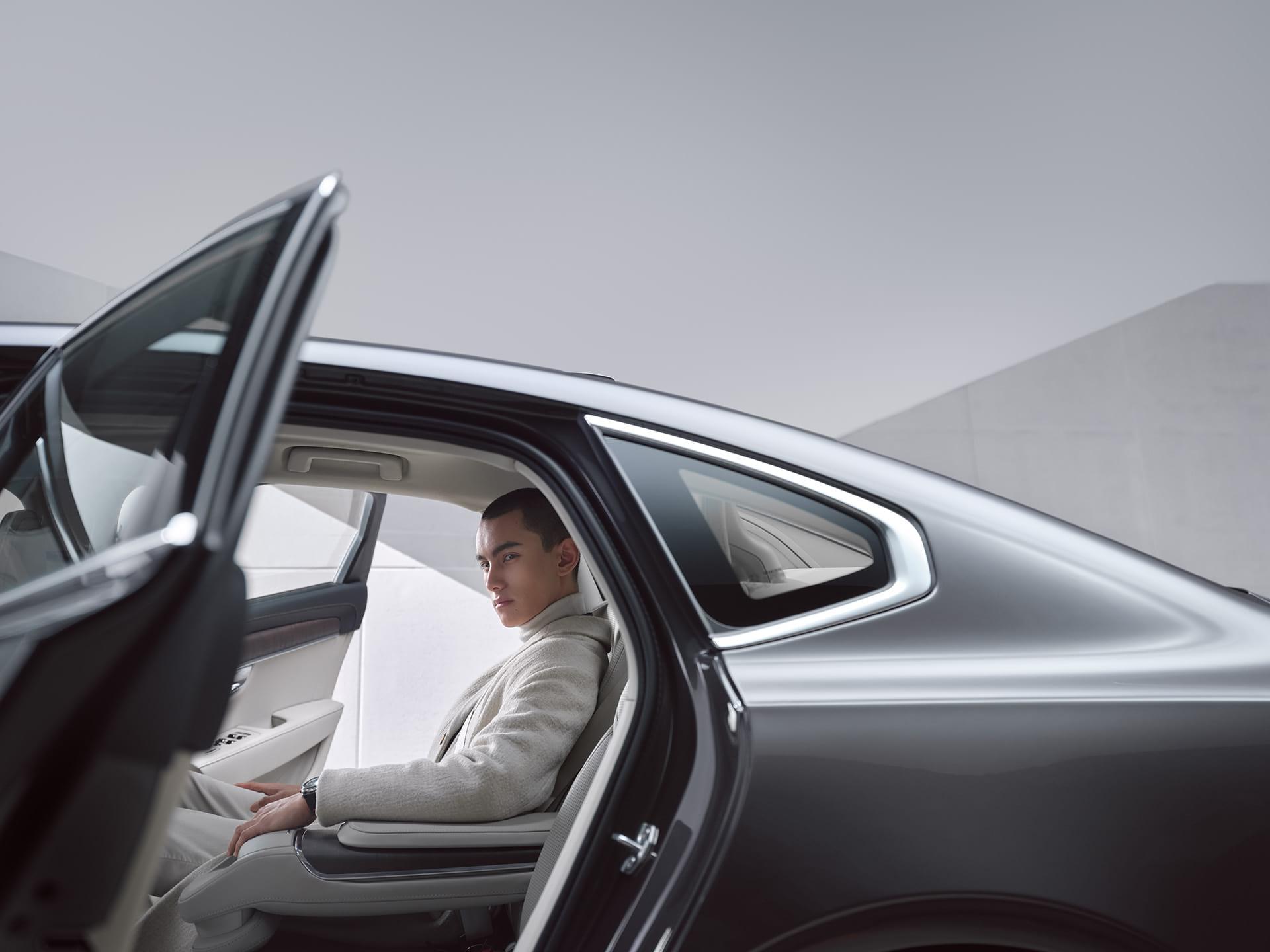 Un bărbat stă așezat pe bancheta din spate a unui Volvo S90 Recharge.