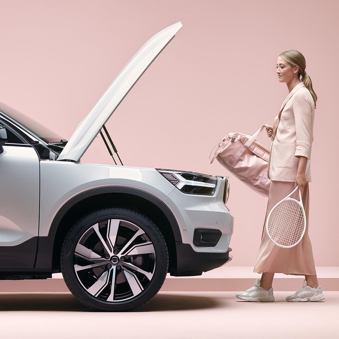 O fată blondă, cu o geantă sport și o rachetă de tenis în mână, se îndreaptă către mașina ei XC40 Recharge