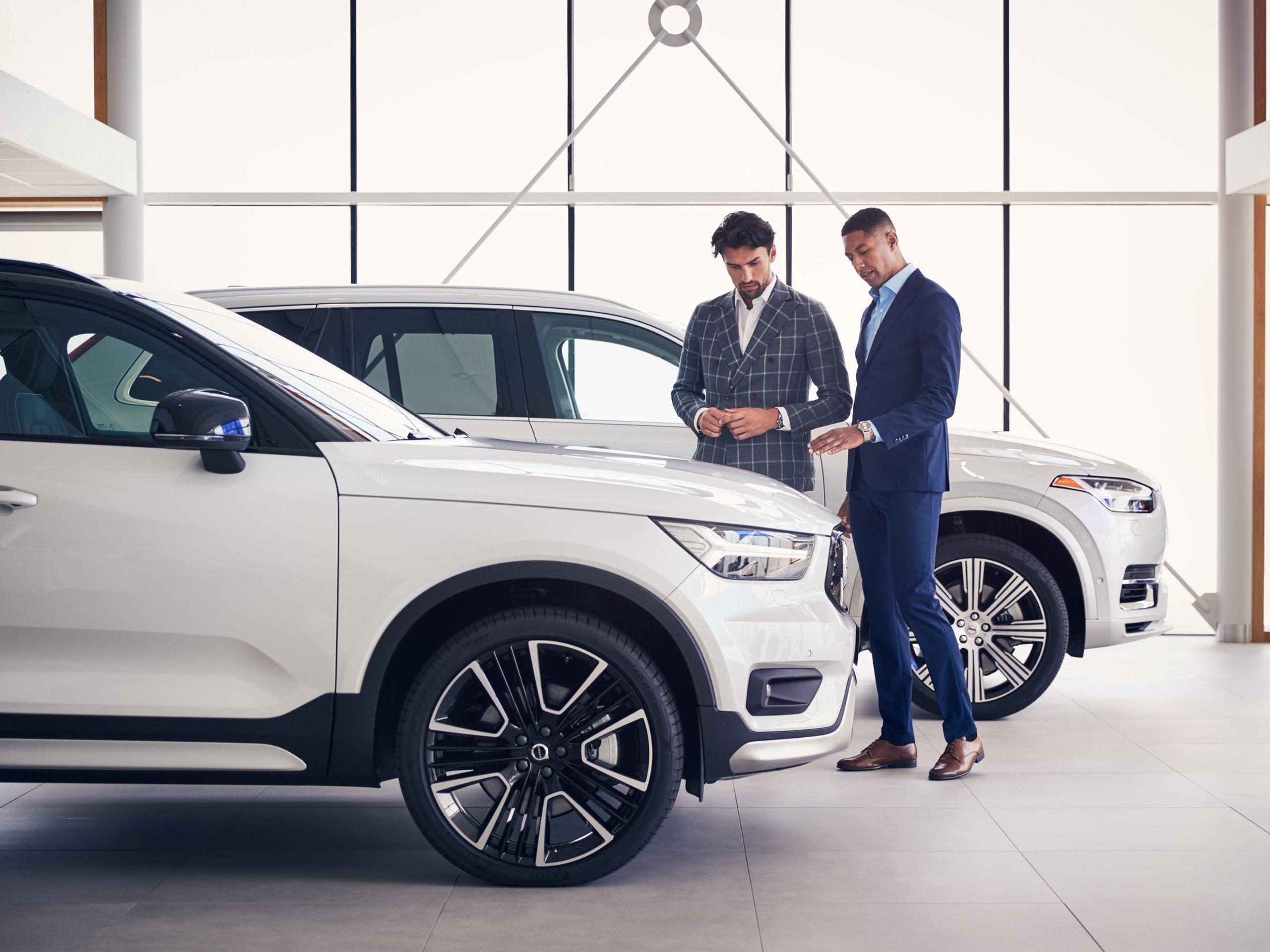 Två män som tittar på en Volvo hos en Volvohandlare.