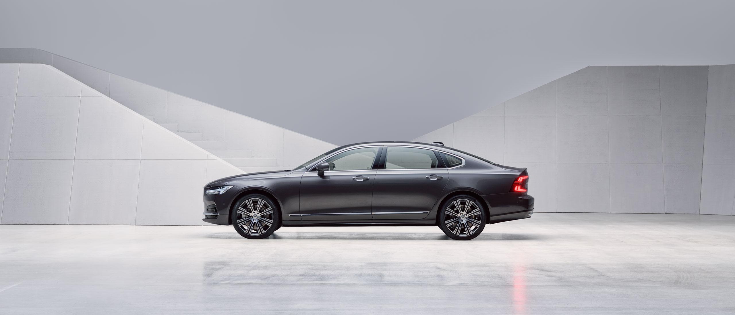 En mörk Volvo S90 är parkerad framför en grå vägg.