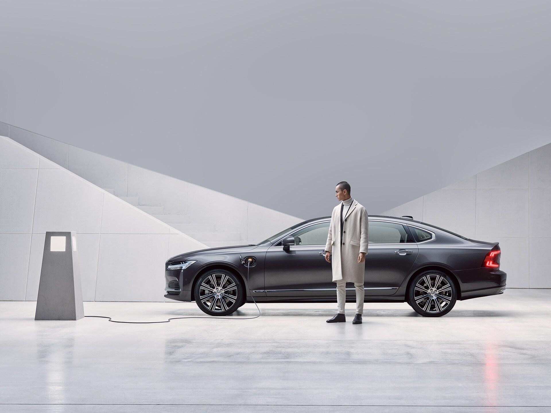 En man står framför sin grå Volvo S90 Recharge, som laddas.