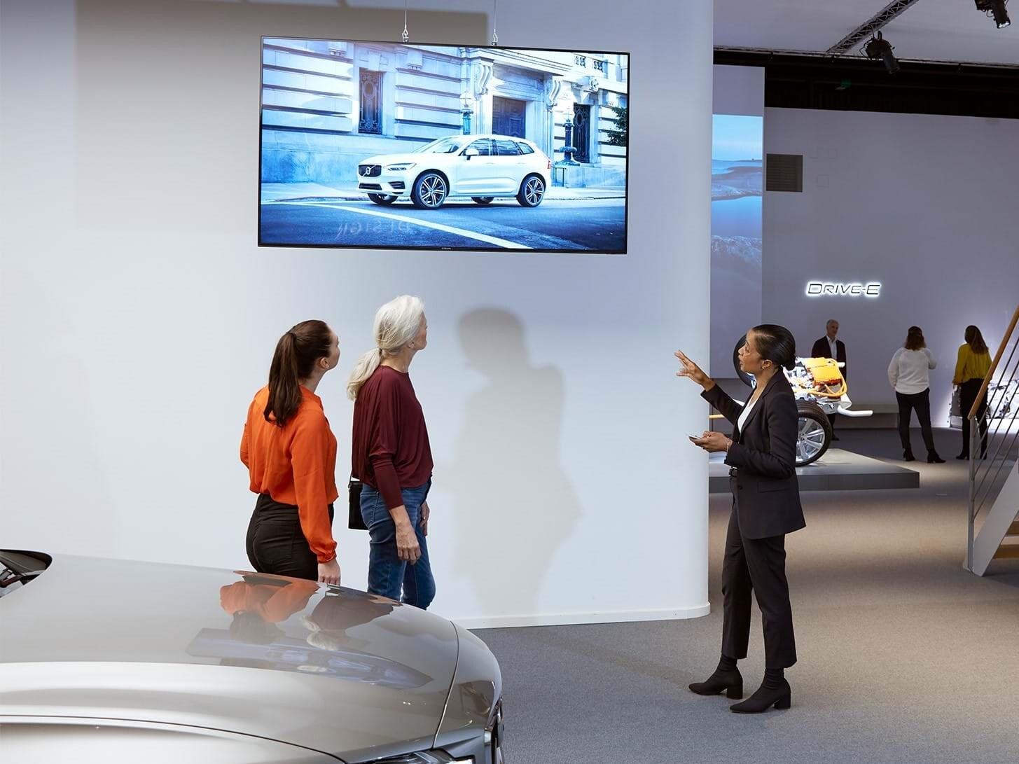 Människor som tittar på en skärm i utställningen på Volvo Cars Brand Experience Center.