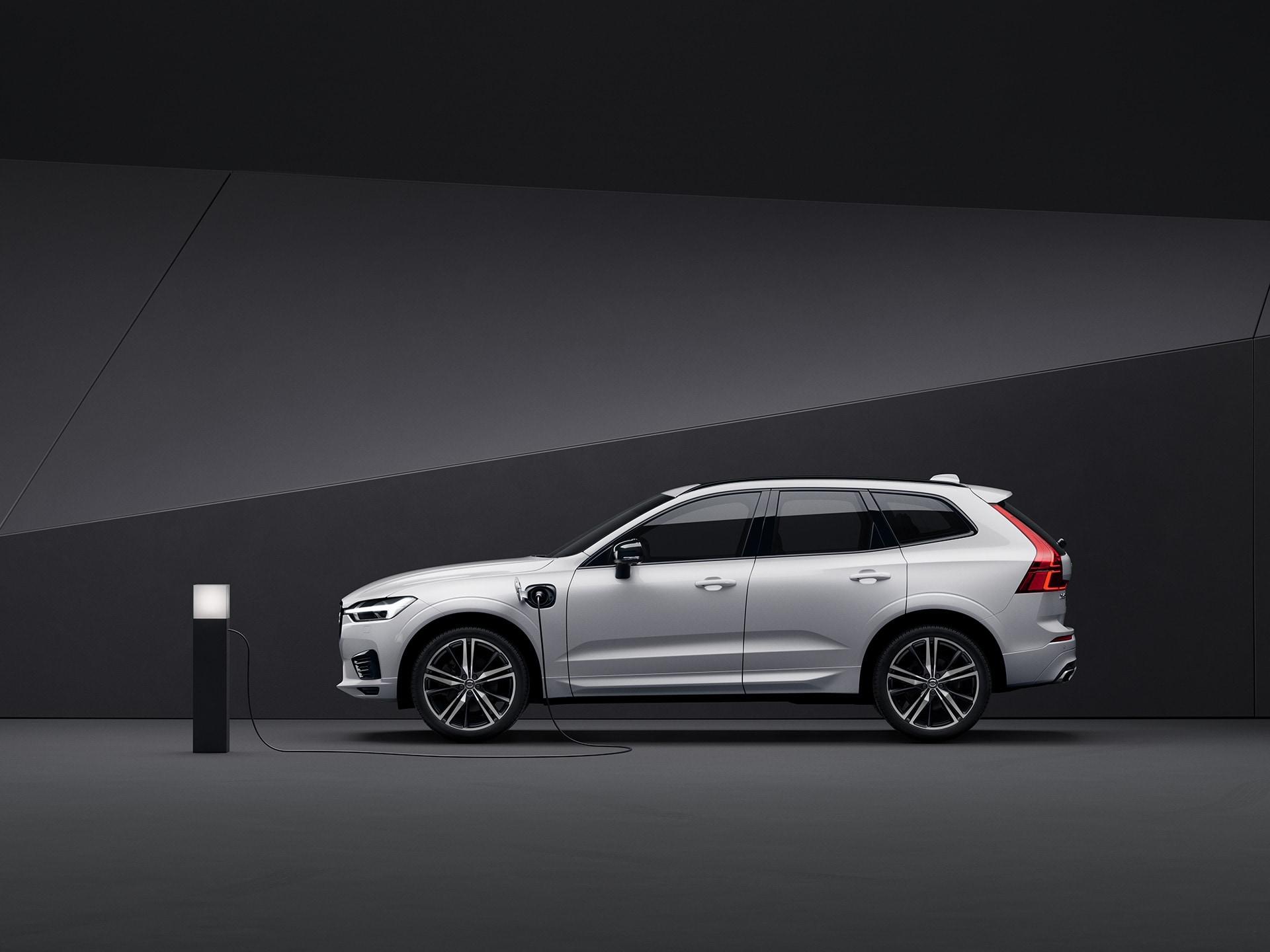 Volvo XC60 Recharge สีขาวกำลังชาร์จไฟท่ามกลางฉากสีดำ