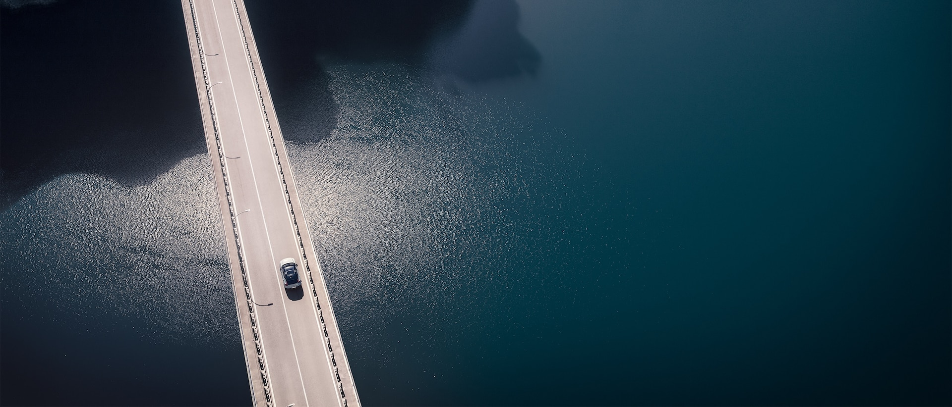 Aerial view of a new Volvo XC40 Recharge Pure Electric SUV as it crosses a two-lane bridge high above calm, dark grey water, heading for a tunnel.