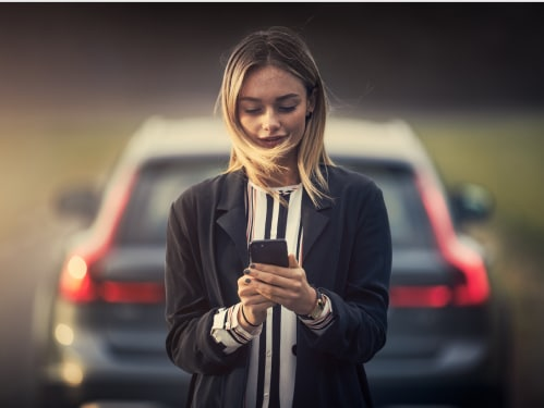 Woman standing in front of a new Volvo SUV, using a smartphone to access the Volvo Valet app