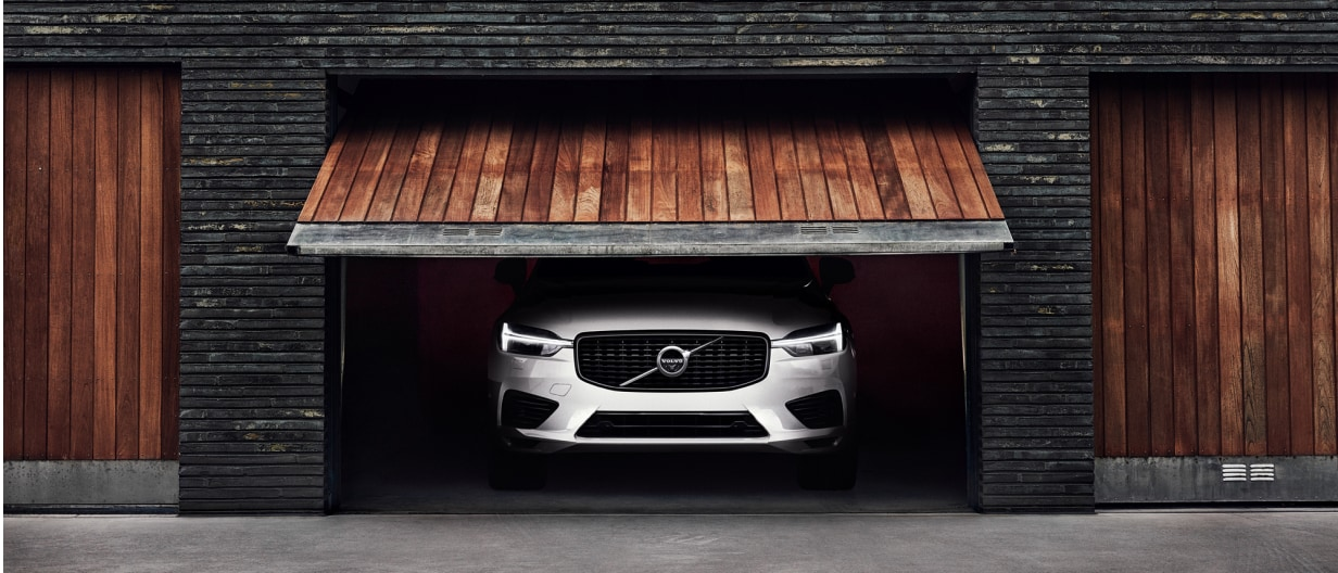 Garage door opening to reveal the front end of a new Volvo XC60