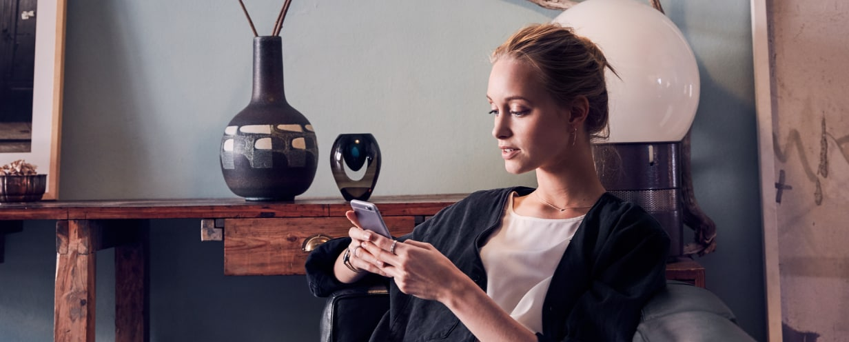 Woman seated in living room, using a smartphone to schedule an appointment with the Volvo Valet app
