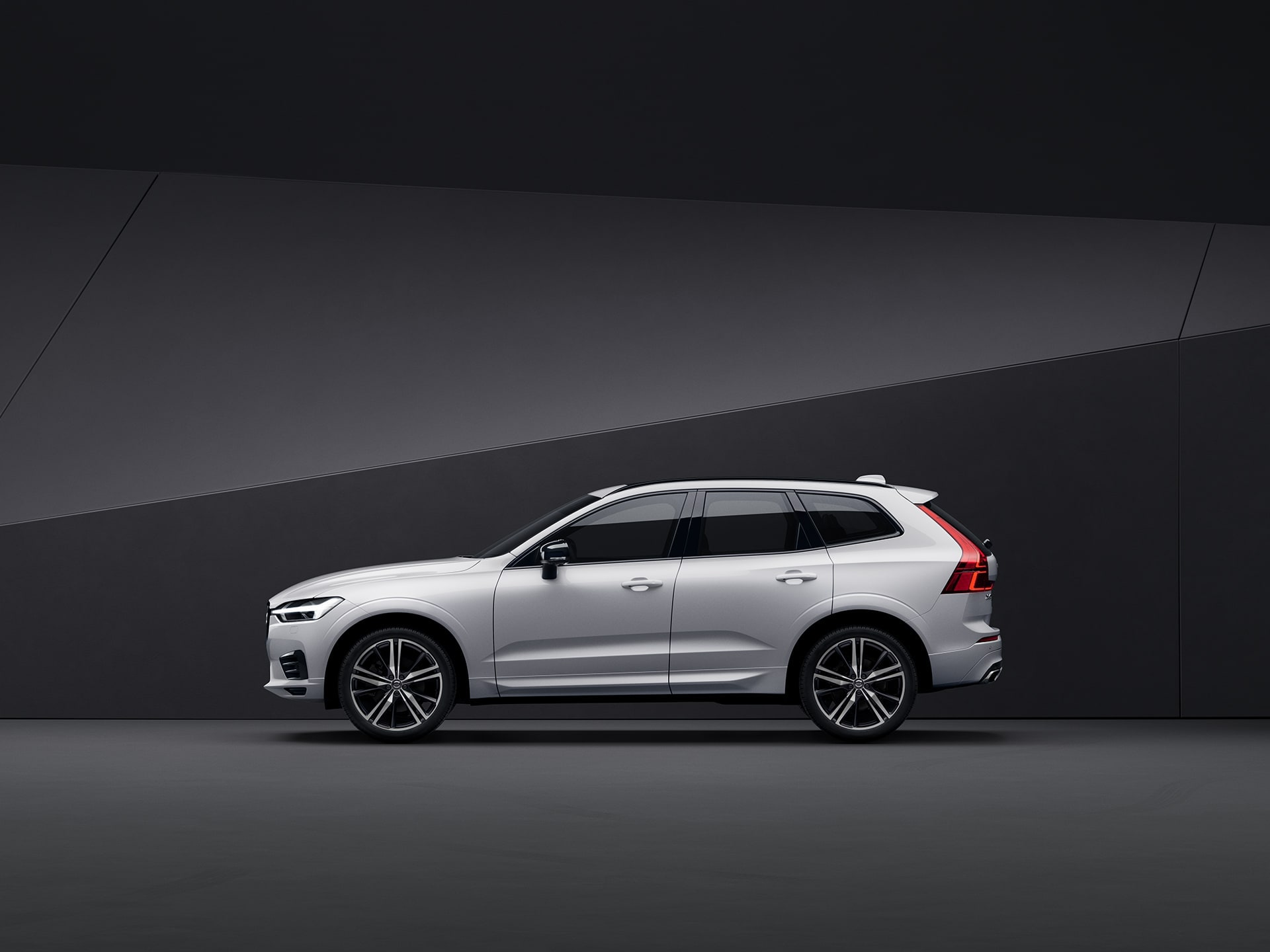 以黑色背景襯托的白色 Volvo XC60 SUV。