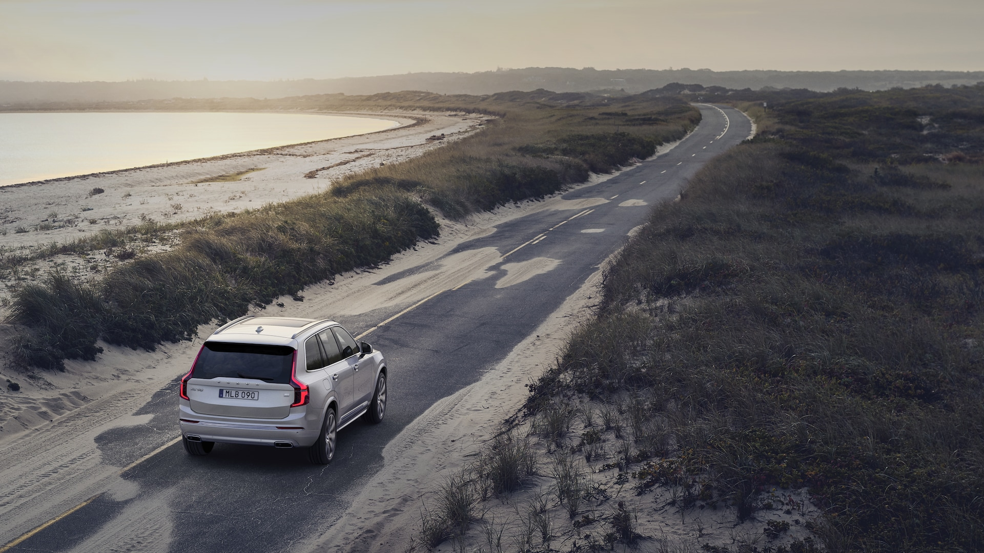 XC90 driving on a beach road at sunset