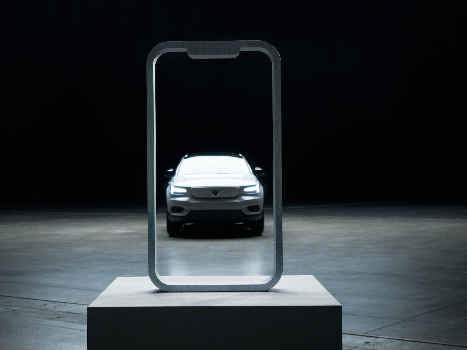 A Volvo XC40 Recharge framed by the outline of a mobile screen set on a podium.