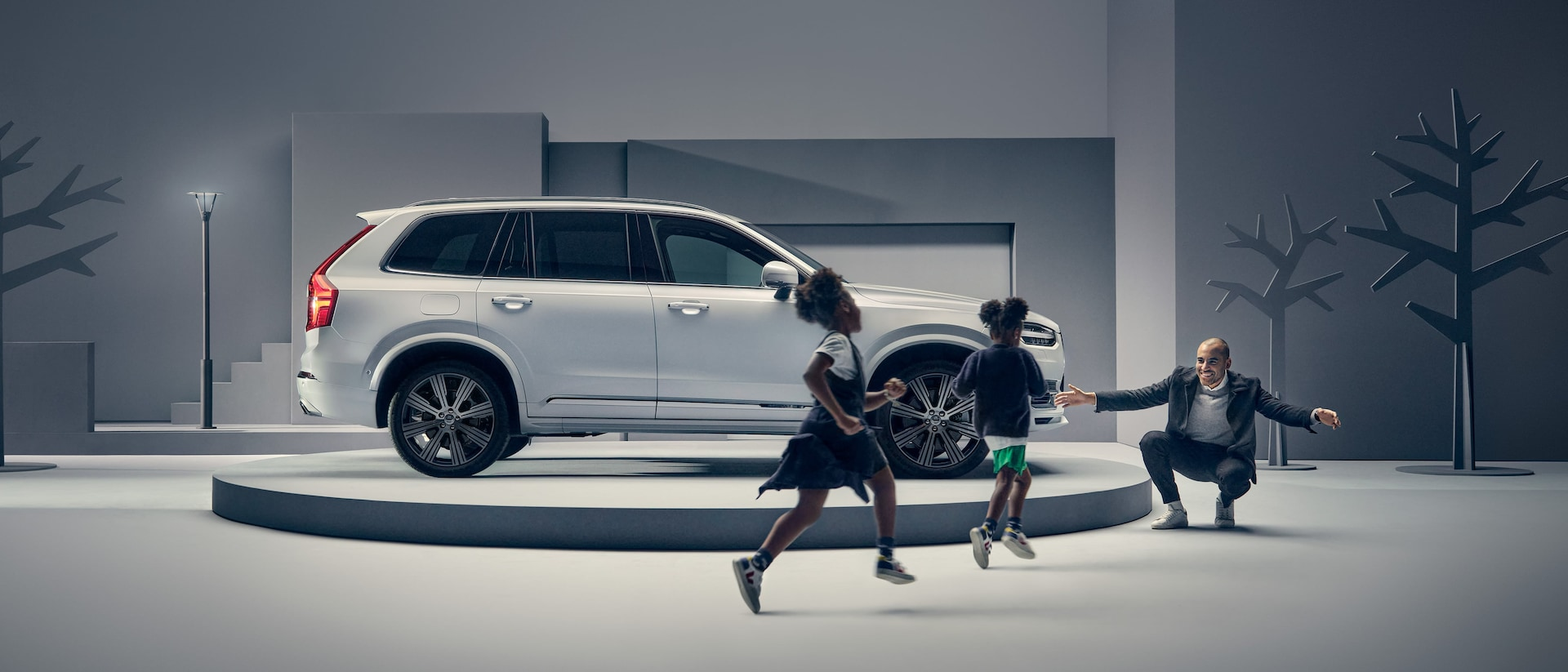 A man greets two children in front of a Volvo on a podium.