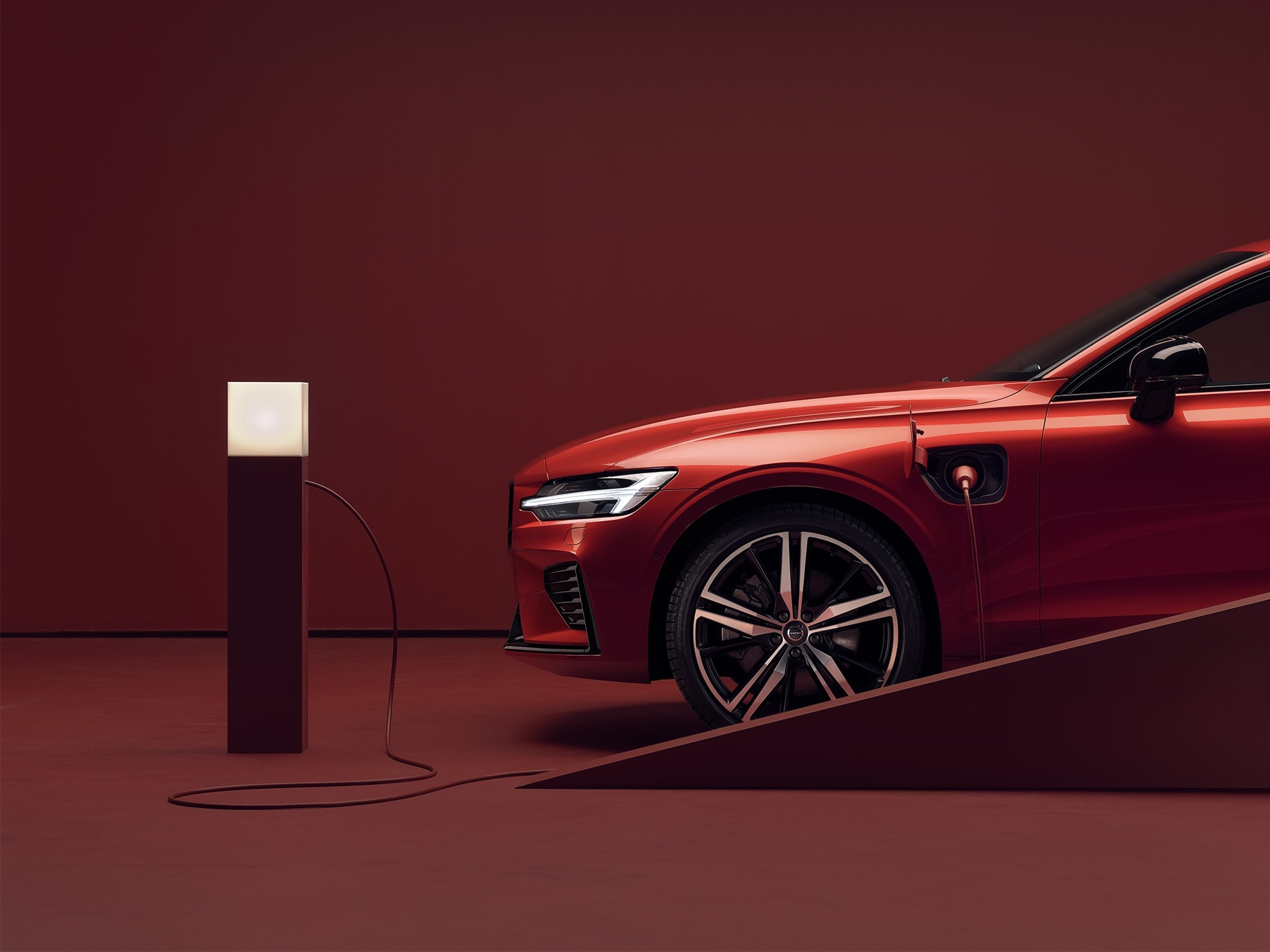 A parked red Volvo sedan is plugged into a charging point