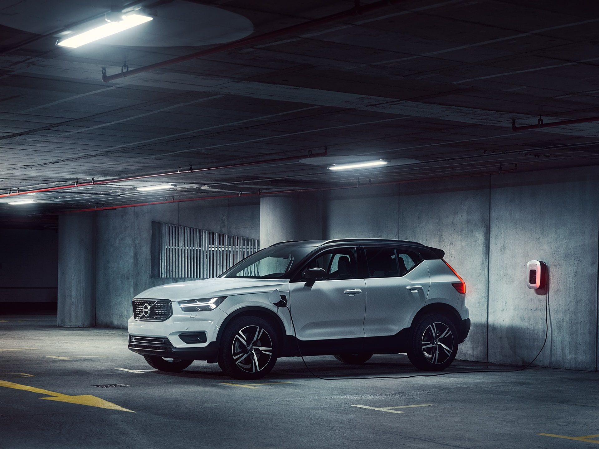 A white XC40 Recharge plug in hybrid parked inside a garage and being charged