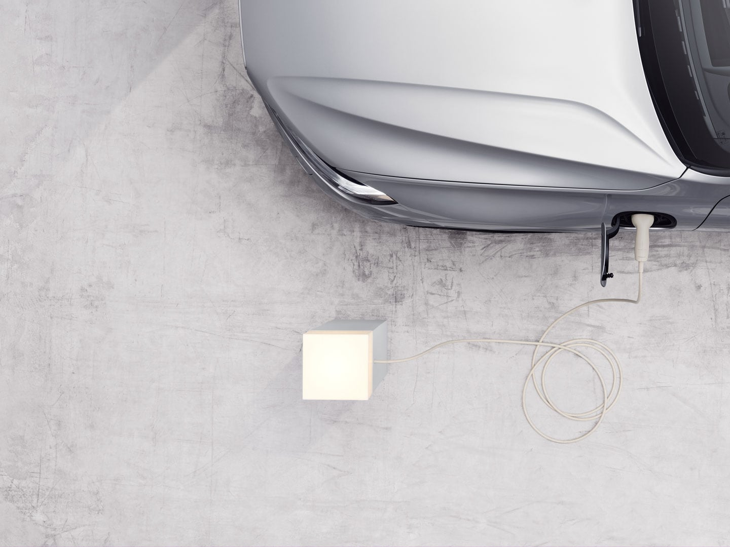 A Volvo Recharge car plugged in to a charging box.