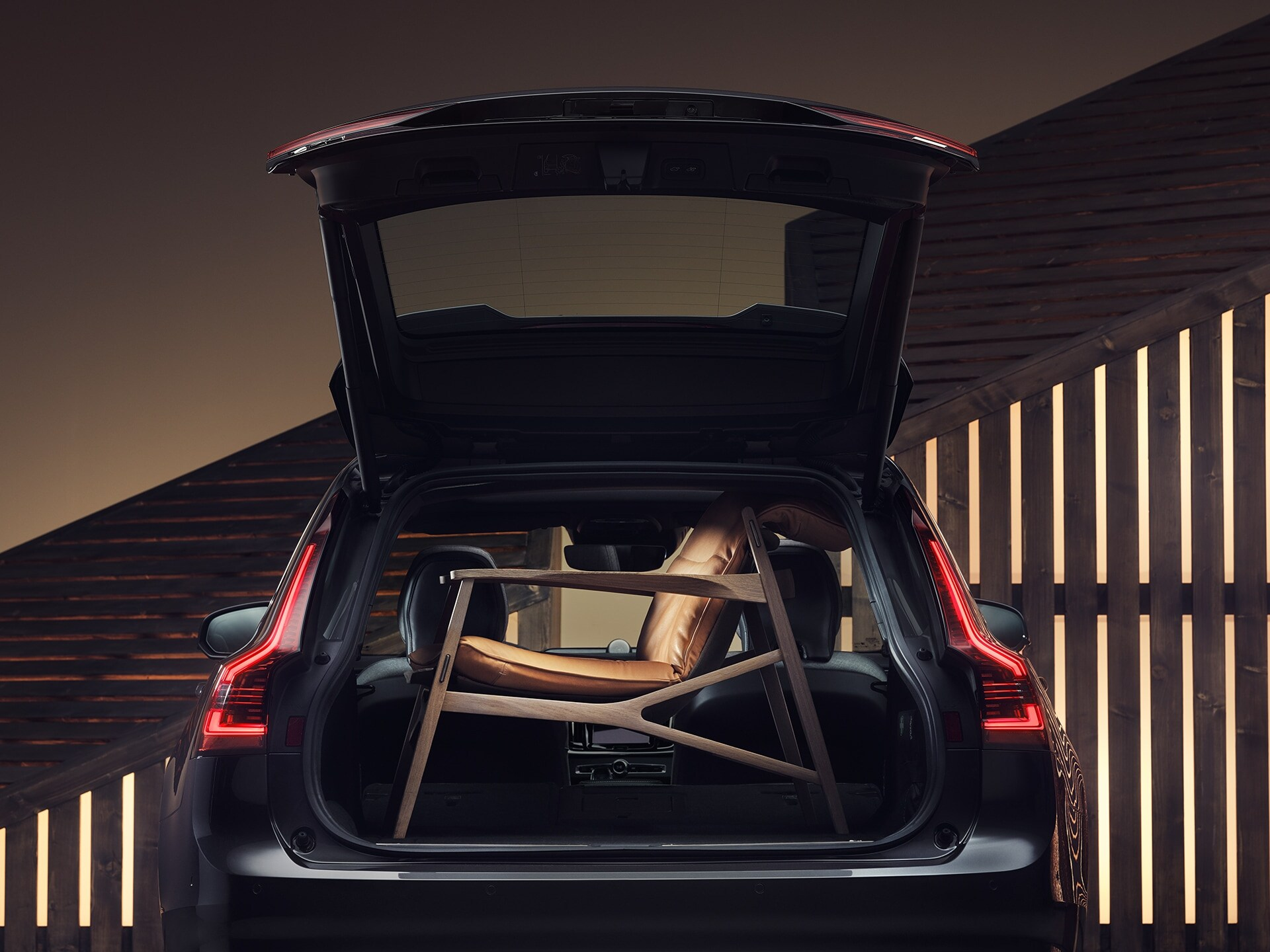 The boot space of a Volvo V90, filled up by an elegant, brown armchair.