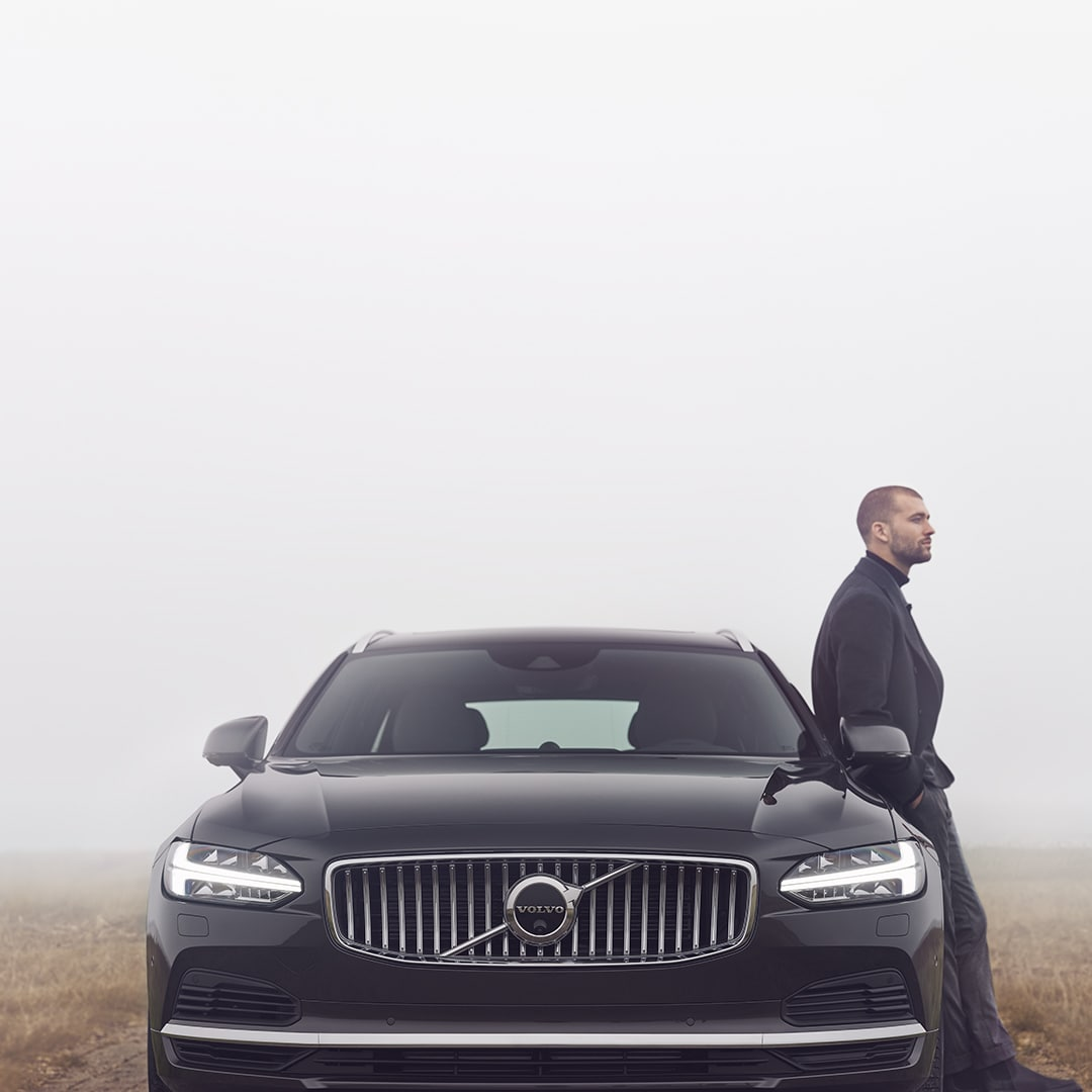 A man is leaning against his Volvo V90, it's cloudy outside.