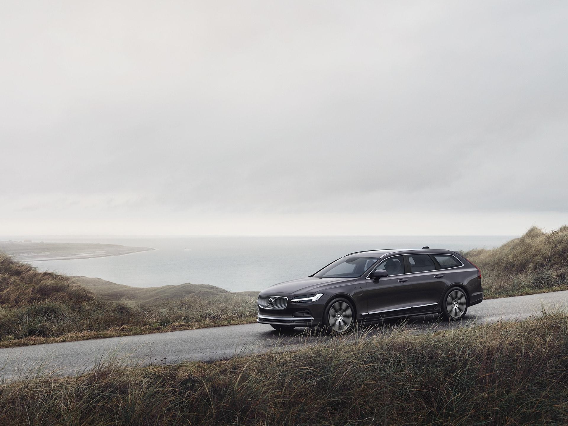 A Volvo V90 mild hybrid driving on a coastal road.
